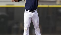 San Diego Padres shortstop Everth Cabrera reaches up high for a throw from the catcher as the infielders participate in pick-off drills during baseball spring training Friday, Feb. 21, 2014, in Peoria, Ariz. (AP Photo/Tony Gutierrez)