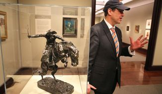 FILE - In this Jan. 27, 2014 file photo, Denver Art Museum Director Christoph Heinrich leans against a Frederic Remington bronze statue of a cowboy riding a bucking horse, part of a collection on display at the Denver Art Museum. The museum is packing up the prized statue to send it to the Seattle Art Museum after losing a friendly Super Bowl bet.  The Seattle Seahawks beat the Denver Broncos 43-8, and the Remington will go to Seattle for three months. (AP Photo/Brennan Linsley, File)