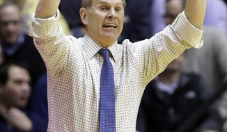 Michigan head coach John Beilein calls a play for his team as they play Purdue in the first half of an NCAA college basketball game in West Lafayette, Ind., Wednesday, Feb. 26, 2014. (AP Photo/Michael Conroy)