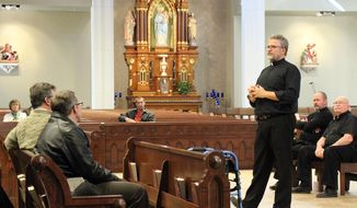 In this photo taken on Sunday, Feb. 23, 2014,, the Rev. Kevin Richter, priest of St. Joseph Catholic Church in Le Mars, speaks with congregants in Le Mars, Iowa, about the unification of the parishes of St. Joseph and St. James Catholic churches. Seated behind him are  Monsignor Mark Duchaine, second from right, of Assumption Church in Merrill, St. Joseph in Struble and St. Joseph in Ellendale, and the Rev. Paul Eisele, of St. James Church in Le Mars. (AP Photo/Le Mars Daily Sentinel, Bennet Goldstein)