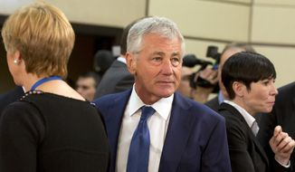 U.S. Secretary of Defense Chuck Hagel, center, arrives for a meeting of defense ministers of the North Atlantic Council at NATO headquarters in Brussels on Wednesday, Feb. 26, 2014. Frustrated with his Afghan counterpart, U.S. President Barack Obama is ordering the Pentagon to accelerate planning for a full U.S. troop withdrawal from Afghanistan by the end of this year. But Obama is also holding out hope that Afghanistan's next president may eventually sign a stalled security agreement that could prevent the U.S. from having to take that step. (AP Photo/Virginia Mayo)