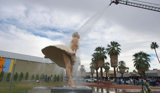 """File-This Jan. 23, 2013 file photo shows the """"Forever Marilyn"""" sculpture getting a shower from the Palm Springs Fire Department in Palm Springs, Calif. The massive statue of Marilyn Monroe that has turned heads for two years in Palm Springs is headed east. The 26-foot-tall, 34,000-pound statue will be transported next month to Hamilton, N.J., where it will be part of an exhibit honoring its designer, Seward Johnson. (AP Photo/The Desert Sun, Jay Calderon,File)   RIVERSIDE PRESS-ENTERPRISE OUT;  NO SALES; NO FOREIGN"""
