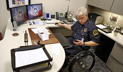 Lt. Tony Crawford checks a message on his mobile phone while working at the Dallas Police Department Jack Evans Police Headquarters building Tuesday, Feb. 25, 2014 in Dallas. Crawford was shot in the line of duty more than two decades ago while working patrol in Lakewood. The bullet severed his spinal column, paralyzing him from the waist down. Crawford returned to desk duty the following year after extensive rehabilitation.  (AP Photo/The Dallas Morning News, G.J. McCarthy)  MANDATORY CREDIT; MAGS OUT; TV OUT; INTERNET USE BY AP MEMBERS ONLY; NO SALES