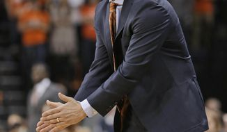 Virginia coach Tony Bennett talks to his players during the first half of an NCAA college basketball game against Miami in Charlottesville, Va., Wednesday, Feb. 26, 2014. (AP Photo/Steve Helber)
