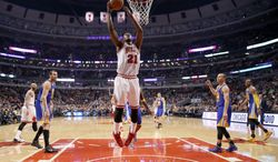 Chicago Bulls shooting guard Jimmy Butler (21) scores during the first half of an NBA basketball game against the Golden State Warriors, Wednesday, Feb. 26, 2014, in Chicago. (AP Photo/Charles Rex Arbogast)