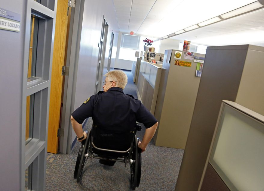 Dallas police Lt. Tony Crawford pushes himself to his office at the Dallas Police Department Jack Evans Police Headquarters building Tuesday, Feb. 25, 2014 in Dallas. Crawford was shot in the line of duty more than two decades ago while working patrol in Lakewood. The bullet severed his spinal column, paralyzing him from the waist down. Crawford returned to desk duty the following year after extensive rehabilitation.  (AP Photo/The Dallas Morning News, G.J. McCarthy)  MANDATORY CREDIT; MAGS OUT; TV OUT; INTERNET USE BY AP MEMBERS ONLY; NO SALES