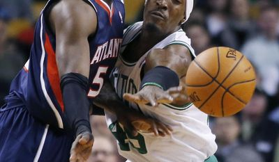 Atlanta Hawks forward DeMarre Carroll, left, passes the ball under pressure from Boston Celtics forward Gerald Wallace during the first quarter of an NBA basketball game in Boston, Wednesday, Feb. 26, 2014. (AP Photo/Elise Amendola)