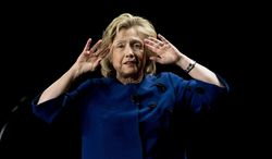 Hillary Rodham Clinton, holding her hand hear her face, speaks to a group of supporters and University of Miami students, Wednesday, Feb. 26, 2014, at the university in Coral Gables, Fla. (AP Photo/J Pat Carter)