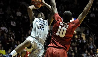 Mississippi guard Jarvis Summers (32) shoots the ball as Alabama forward Jimmie Taylor (10) guards during the second half of an NCAA college basketball game in Oxford, Miss., Wednesday, Feb. 26, 2014. Mississippi won 79-67. (AP Photo/Thomas Graning)
