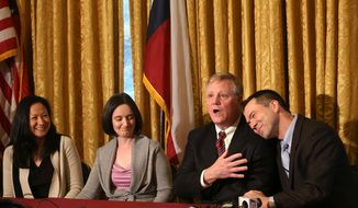 Gay couples from left, Cleopatra De Leon and Nicole Dimetman, and Mark Phariss and Victor Holmes, give a news conference in San Antonio on Wednesday, Feb. 26, 2014 after U.S. Federal Judge Orlando Garcia declared a same-sex marriage ban in deeply conservative Texas unconstitutional. (AP Photo/San Antonio Express-News, Jerry Lara)