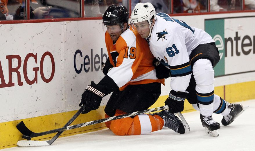 Philadelphia Flyers' Scott Hartrnell, left, and San Jose Sharks' Justin Braun, right, dig for the puck along the boards during the second period of an NHL hockey game on Thursday, Feb. 27, 2014, in Philadelphia. (AP Photo/Tom Mihalek)