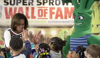 First lady Michelle Obama high-fives children after exercising and dancing with the Super Sprowtz during a visit to La Petite Academy in Bowie, Md., Thursday, Feb. 27, 2014,  to show and talk about healthy environments and encouraging healthy habits at preschools as part of her Let's Move! Child Care program. (AP Photo/Carolyn Kaster)