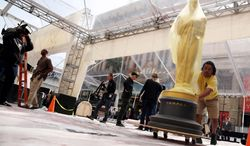 Johnny Tamayo pushes an Oscar statue as preparations are made for the 86th Academy Awards in Los Angeles, Thursday, Feb. 27, 2014. The Academy Awards will be held at the Dolby Theatre on Sunday, March 2. (Photo by Matt Sayles/Invision/AP)