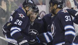 Winnipeg Jets' Blake Wheeler (26), Bryan Little (18) Dustin Byfuglien (33) and Andrew Ladd (16) celebrate Little's goal against the Phoenix Coyotes during second-period NHL hockey game action in Winnipeg, Manitoba, Thursday, Feb. 27, 2014. (AP Phoyo/The Canadian Press, John Woods)