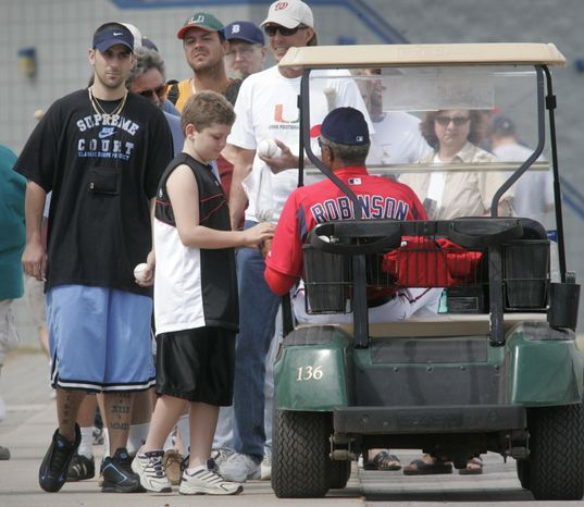 Washington Nationals baseball manager Frank Robinson, right, signs an autograph for Alex Fuoco, 12, from Palm Bay, Fla. during spring training, Saturday, Feb. 26, 2005, in Viera, Fla.(AP Photo/Lawrence Jackson)