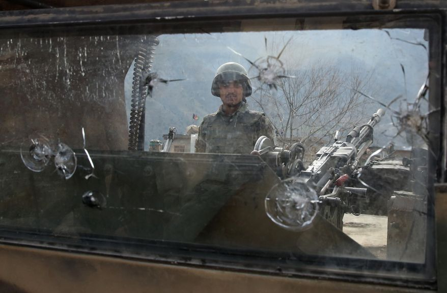 AP10ThingsToSee - An Afghan National Army soldier stands guard on a military vehicle in the Narai military camp in the Ghazi Abad district in Kunar province, Afghanistan on Monday, Feb. 24, 2014. Taliban insurgents attacked army checkpoints in the area on Sunday, Feb. 23, killing 21 soldiers. It was the deadliest single incident for the Afghan army in at least a year. (AP Photo/Massoud Hossaini, File)