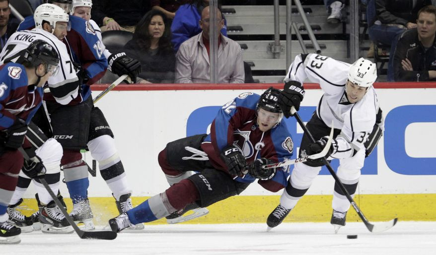 Colorado Avalanche left wing Gabriel Landeskog (92) reaches for Los Angeles Kings defenseman Willie Mitchell (33) in the second period of an NHL game on Wednesday, Feb. 26, 2014 in Denver. (AP Photo/Joe Mahoney)