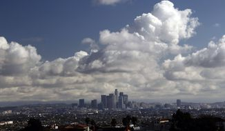 Storm clouds are shown over downtown Los Angeles Thursday Feb. 27, 2014. Southern California got an overnight soaking Thursday as residents prepared for a second, more powerful storm that could bring heavier rain and prompted fears of mudslides in communities along fire-scarred foothills.(AP Photo/Nick Ut)