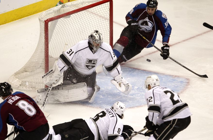 Los Angeles Kings goalie Martin Jones (31) watches the puck pass through the crease as Colorado Avalanche left wing Patrick Bordeleau (58) collides with the goal in the first period of an NHL game, Wednesday, Feb. 26, 2014 in Denver. (AP Photo/Joe Mahoney)