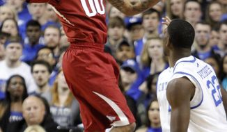 Arkansas' Rashad Madden looks for an open teammate as Kentucky's Alex Poythress (22) watches during the first half of an NCAA college basketball game Thursday, Feb. 27, 2014, in Lexington, Ky. (AP Photo/James Crisp)