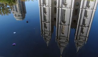 """FILE - In this Sept. 30, 2012, file photo, the Mormon temple in Salt Lake City is reflected in a pool. A newly-posted article, part of a series of recent online articles posted on the website of The Church of Jesus Christ of Latter-day Saints, affirms the faith's belief that humans can become like God in eternity, but explains that the """"cartoonish image of people receiving their own planets"""" is not how the religion envisions it. (AP Photo/Shannon Dininny, File)"""