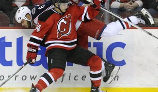 New Jersey Devils' Adam Henrique (14) checks Columbus Blue Jackets' Nathan Horton during the first period of an NHL hockey game on Thursday, Feb. 27, 2014, in Newark, N.J. (AP Photo/Bill Kostroun)