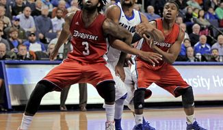Saint Louis' Dwayne Evans, center, can't get through the defense of Duquesne's Dominique McKoy (3) and Jerry Jones (5) during the second half of an NCAA college basketball game, Thursday, Feb. 27, 2014, in St. Louis. Duquesne beat Saint Louis 71--64. (AP Photo/Tom Gannam)