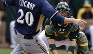 Oakland Athletics catcher Derek Norris, right, drops the ball as Milwaukee Brewers' Jonathan Lucroy slides safely into home during the third inning of a spring training baseball game on Thursday, Feb. 27, 2014, in Scottsdale, Ariz. (AP Photo/Gregory Bull)