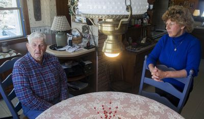 In this Feb. 10, 2014 photo, Judy Bates listens as her husband, Roger, talks about being rescued from his grain bin on Jan. 31 in Rockton, Ill. The 78-year-old sank neck-deep into 35,000 bushels of corn while trying to break up spoiled clumps of material that would have clogged the machines. (AP Photo/Rockford Register Star, Max Gersh)  MANDATORY CREDIT