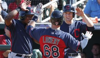 Cleveland Indians' Jake Lowery (68) is congratulated by Carlos Moncrief, left, and David Adams after hitting a grand slam against the Cincinnati Reds in the fifth inning of an exhibition baseball game in Goodyear, Ariz., Thursday, Feb. 27, 2014. (AP Photo/Paul Sancya)