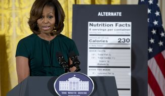 First lady Michelle Obama speaks in the East Room of the White House in Washington, Thursday, Feb. 27, 2014, about helping parents and other consumers make healthier choices as part of her Let's Move program. The Obama administration is proposing new food labels that would make it easier to know about calories and added sugars, a reflection of the shifting science behind nutrition.  (AP Photo/Carolyn Kaster)
