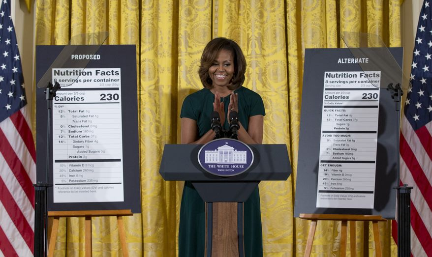 First lady Michelle Obama, flanked by enlargements of a proposed nutrition label, left, and a proposed alternate label, claps as she speaks during in the East Room of the White House in Washington, Thursday, Feb. 27, 2014, about helping parents and other consumers make healthier choices as part of her Let's Move program. The Obama administration is proposing new food labels that would make it easier to know about calories and added sugars, a reflection of the shifting science behind nutrition.  (AP Photo/Carolyn Kaster)