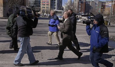 Former Central Falls, RI., mayor Charles Moreau is followed by members of the media as he leaves the Federal Courthouse and walks to his car in Providence, RI., Friday, Feb. 28, 2014. Moreau was released from federal prison Friday after serving just under one year of a two-year sentence.   Moreau was released after first pleading guilty to a new charge of accepting a bribe and being sentenced on that charge to time served. As part of the deal, U.S. District Court Judge John McConnell then vacated Moreau's 2012 conviction, allowing him to walk free.   (AP Photo/Stephan Savoia)