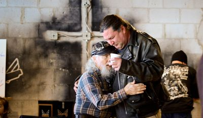 Fred Bennett, left, and Daryl Artist, right, of Viriginia Beach, Va., become emotional as they hug following Sunday mass at Freedom Biker Church, Chesapeake, Va., Sunday February 23, 2014. Years ago Artist stabbed Bennett's son seven times over a dispute and the Bennett family says they have forgiven Artist after they found god. Andrew Harnik/The Washington Times