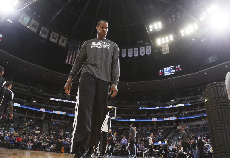 Brooklyn Nets center Jason Collins warms up before facing the Denver Nuggets in an NBA basketball game in Denver on Thursday, Feb. 27, 2014. (AP Photo/David Zalubowski)