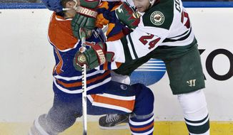 Minnesota Wild's Matt Cooke (24) checks Edmonton Oilers' Andrew Ference (21) during second period NHL hockey action in Edmonton, Canada, Thursday, Feb. 27, 2014. (AP Photo/The Canadian Press, Jason Franson)