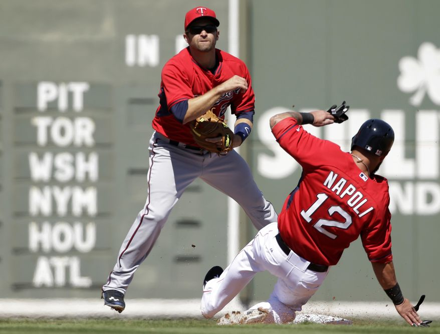 Minnesota Twins second baseman Brian Dozier, left, throws to first to complete a double play as Boston Red Sox first baseman Mike Napoli, right, slides out at second in the second inning of an exhibition baseball game Friday, Feb. 28, 2014, in Fort Myers, Fla. (AP Photo/Steven Senne)