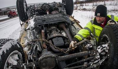 Smitty's Towing and Service Tow Truck driver Kevin Smith, 47, of Burton, Mich., hooks some chains to a rolled over 2004 Jeep Wrangler as he removes it from the side of the road on Thursday, Feb. 27, 2014 on Interstate 69 westbound near the Belsay Road exit in Burton., Mich. (AP Photo/The Flint Journal, Jake May)
