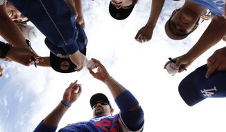 Los Angeles Dodgers first baseman Adrian Gonzalez signs autographs before an exhibition baseball game against the Chicago White Sox in Glendale, Ariz., Friday, Feb. 28, 2014. (AP Photo/Paul Sancya)