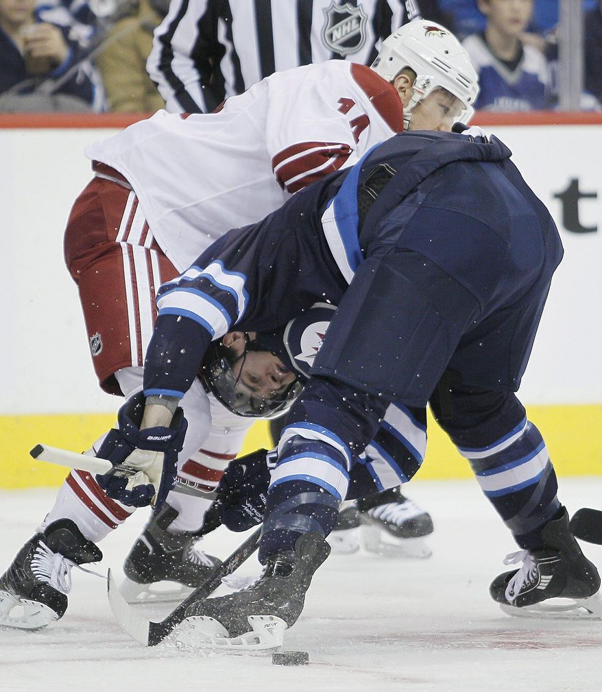 Phoenix Coyotes' Jeff Halpern (14) checks Winnipeg Jets' Mark Scheifele during a face-off during second-period NHL hockey game action in Winnipeg, Manitoba, Thursday, Feb. 27, 2014. (AP Photo/The Canadian Press, John Woods)
