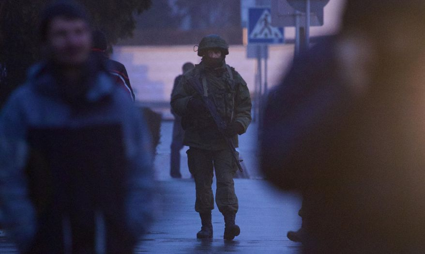 An unidentified armed man patrols a square in front of the airport in Simferopol, Ukraine, Friday, Feb. 28, 2014.  Dozens of armed men in military uniforms without markings occupied the airport in the capital of Ukraine's strategic Crimea region. (AP Photo/Ivan Sekretarev)