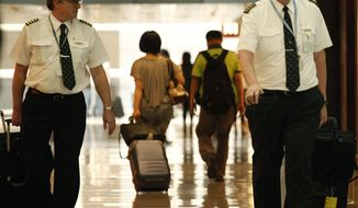 In this Nov. 30, 2011, photo, two pilots from Cathay Pacific walk in the Hong Kong International Airport in Hong Kong.  The U.S. airline industry will need to hire 1,900 to 4,500 new pilots annually over the next 10 years due to an expected surge in retirements of pilots reaching age 65 and increased demand for air travel, the Government Accountability Office said in the report obtained late Thursday, Feb. 27, 2014. (AP Photo/Vincent Yu, File)