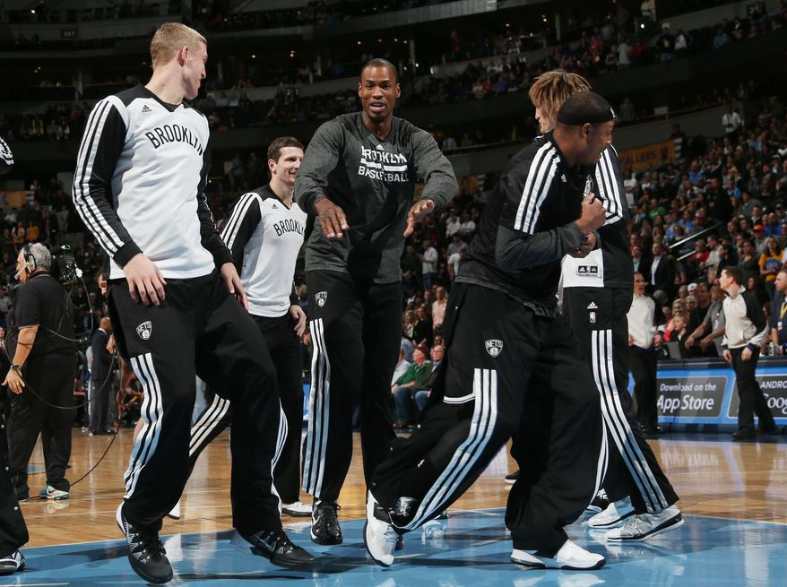 Brooklyn Nets center Jason Collins, center, jokes with teammates during player introductions before the Nets faced the Denver Nuggets in an NBA basketball game in Denver on Thursday, Feb. 27, 2014. (AP Photo/David Zalubowski)