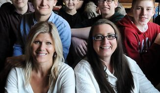ADVANCE FOR MONDAY MARCH 3 AND THEREAFTER.  - Jen True, left, and Heather Sandland are surrounded by sons and nephews in a photo taken Feb. 3, 2014 in Mankato, Minn. True read an article in the Mankato, Minn. Free Press about  Sandland needing a kidney and decided to give her one. Both are healthy and happy today. (AP Photo/Mankato Free Press, John Cross)
