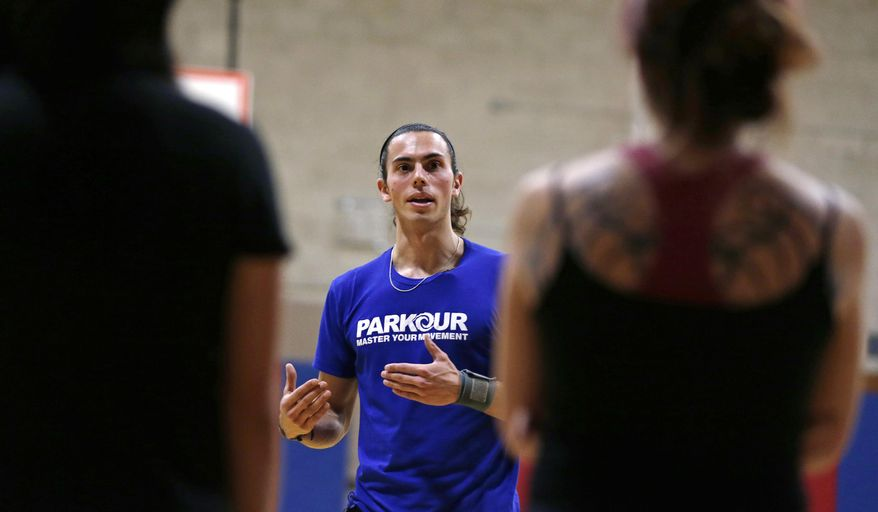 In this Wednesday, Jan. 29, 2014 photo, Blake Evitt, an instructor with Parkour Generations Americas, talks with his students during a Parkour training class in Brookline, Mass.  (AP Photo/Charles Krupa)
