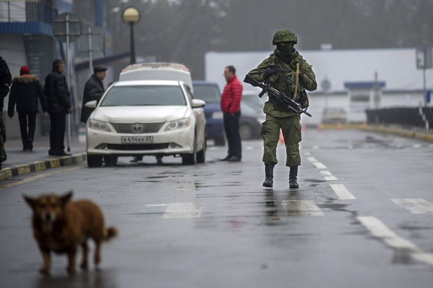 An unidentified armed man patrols a square in front of the airport in Simferopol, Ukraine, Friday, Feb. 28, 2014. Russian military were blocking the airport in the Black Sea port of Sevastopol in Crimea near the Russian naval base while unidentified men were patrolling another airport serving the regional capital, Ukraine's new Interior Minister Arsen Avakov said on Friday. (AP Photo/Andrew Lubimov)