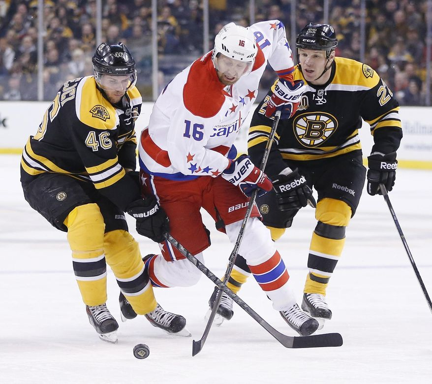 Washington Capitals' Eric Fehr (16) battles Boston Bruins' David Krejci (46) and Shawn Thornton (22) for the puck in the first period of an NHL hockey game in Boston, Saturday, March 1, 2014. (AP Photo/Michael Dwyer)