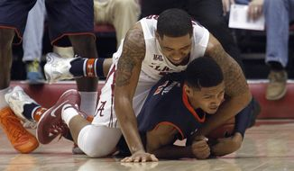 Alabama's Trevor Releford (12) and Auburn's Dion Wade (11) wrestle for a loose ball during the first half of an NCAA college basketball game Saturday, March 1, 2014, in Tuscaloosa, Ala. (AP Photo/Butch Dill)