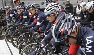 Cyclists of the Swiss IAM team hold a minute of silence for their team mate Kristof Goddaert who was killed in a training crash two weeks ago, prior to the start of the Omloop Het Nieuwsblad, the Belgian opener of the cycling season, in Ghent, western Belgium, Saturday, March 1, 2014. (AP Photo/Yves Logghe)