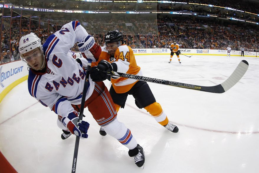 Philadelphia Flyers' Kimmo Timonen, right, shoves New York Rangers' Ryan Callahan into the corner during the first period of an NHL hockey game, Saturday, March 1, 2014, in Philadelphia. (AP Photo/Matt Slocum)
